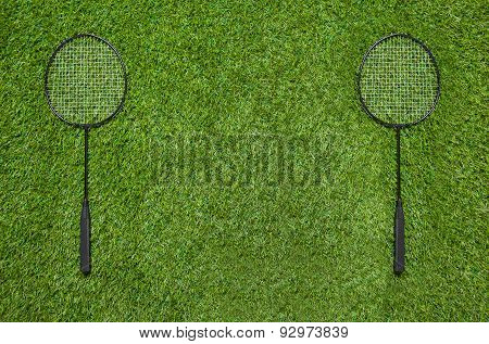 Two badminton rackets lying on the grass
