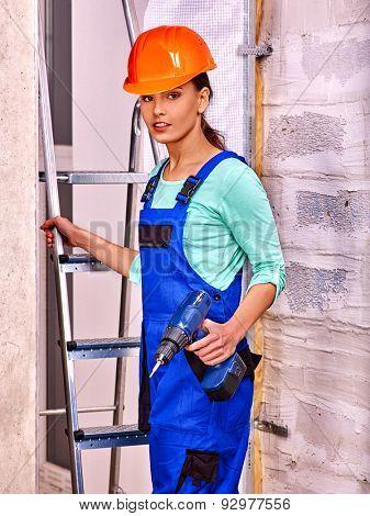 Young woman in blue builder uniform indoor.