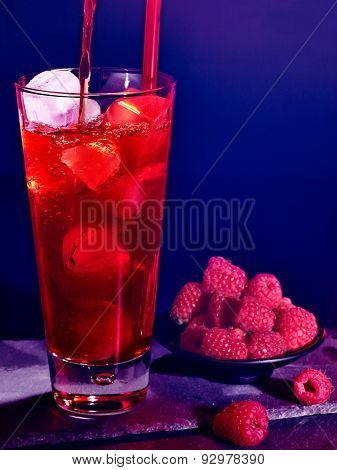 Red raspberry pouring drink  with ice cube on black background. Cocktail card 62.