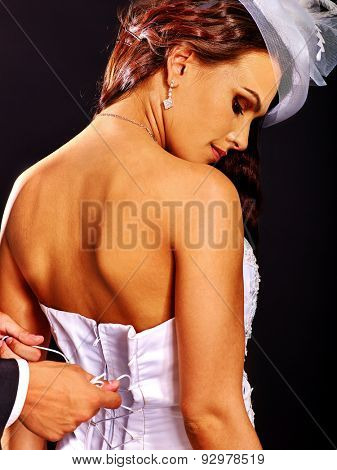 Beautiful bridal trying on wedding dress. Male hands lacing corset.