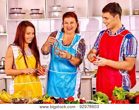 Mature woman with young happy family preparing  dinner at kitchen.