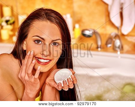 Woman relaxing at home luxury bath and applying moisturize cream on face.