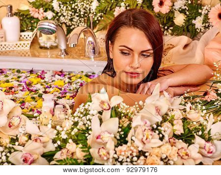 Woman looking down relaxing at water flower spa.