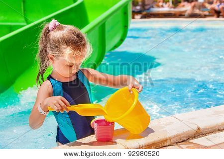 Child with bucket in swimming pool at water park on  summer outdoor.