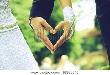 bride and groom hands  in the shape of heart