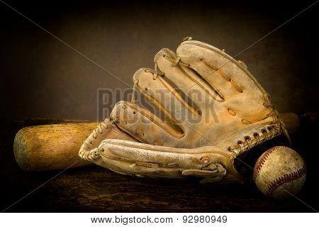 Dark still life with baseball glove, bat and ball