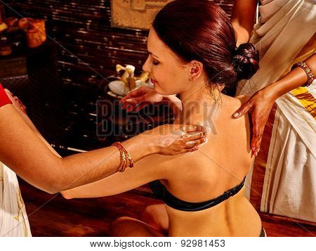 Young woman with bare back having spa treatment.