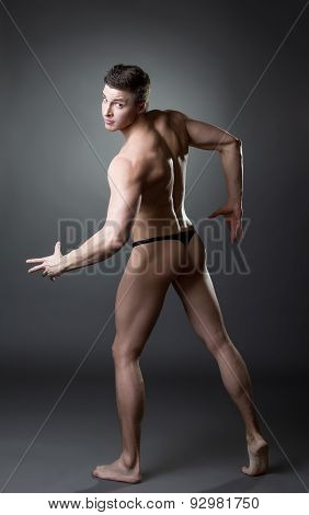 Image of brawny guy posing dressed in thong