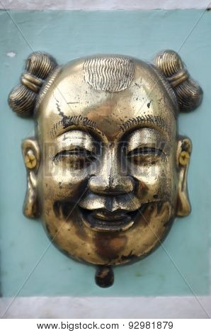 Brass or bronze chinese mask on green cement wall