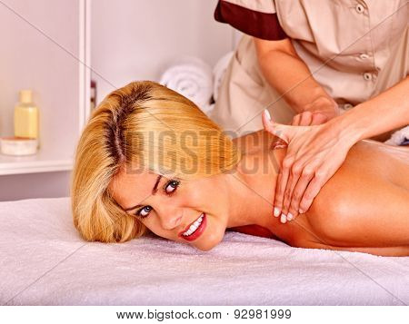 Blond woman getting massage in health resort and looking at camera .