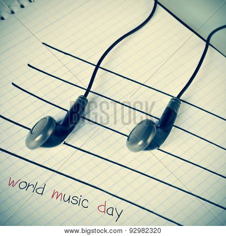 a pair of earphones placed on a staff drawn on a notepad simulating musical notes, and the text world music day