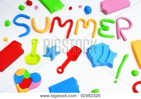 the text summer made from modelling clay of different colors and some beach toys such as toy shovels and sand moulds, on a white background