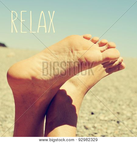 the text relax and the bare feet of a young caucasian man relaxing in a shingle beach, with a retro look