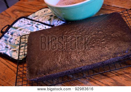 Dark Chocolate Cake Cooling On Rack On Wooden Table