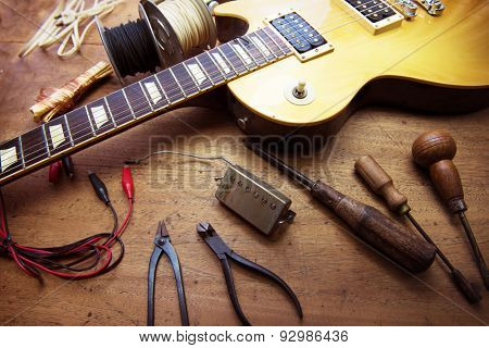 Guitar on guitar repair desk. Vintage electric guitar on a guitar repair work shop. Single cutaway solid body guitar, gold color.