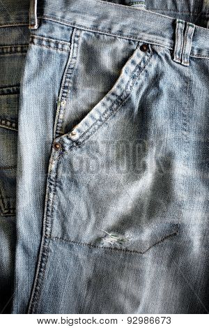 Closeup detail of a washed out blue jeans pocket