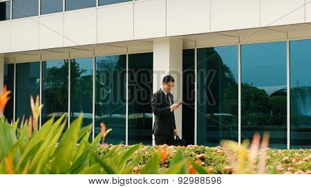 Businessman Chatting On Mobile Phone Walking To Office