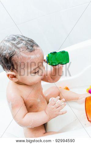 Playful baby boy having a bath
