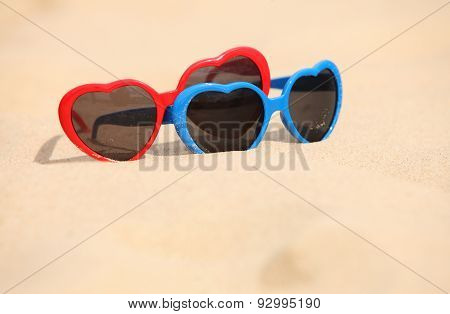 Colorful Sunglasses Shaped Heart On The Sand