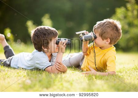Two little boys play with binoculars on the grass