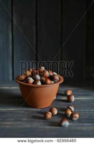Hazel Nuts In A Clay Bowl On A Dark Wooden Surface