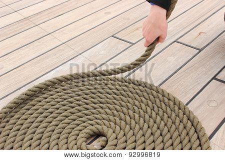 Hand Of Woman And Thick Rope Wrapped In Spiral Lying On Deck Of Ship