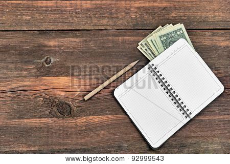 Open Notepad, Pencil And Dollars Cash On Rough Wood Background