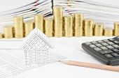 foto of piles  - House and pencil with calculator on finance account have step pile of gold coins around and pile of paperwork as background.