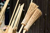 stock photo of gizmo  - New handmade broomsticks leaning against dark wooden wall - JPG