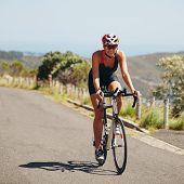 stock photo of triathlon  - Woman triathlon athlete cyclist down hill on country road - JPG