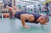 stock photo of suspension  - Handsome man doing hard suspension training with fitness straps in a fitness center - JPG