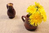picture of vase flowers  - Bouquet of yellow fresh flowers of dandelion in brown vase and empty vase in background lying on jute canvas - JPG