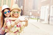 stock photo of selfie  - A picture of two happy girl friends taking selfie in the city - JPG