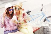 picture of tandem bicycle  - A picture of two girl friends riding a tandem bicycle and taking selfie in the city - JPG