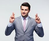 stock photo of fingers crossed  - Happy businessman with fingers crossed over gray background - JPG