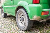 stock photo of mud  - Detail of the rear wheel of a green automobile with mud - JPG