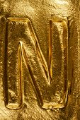 stock photo of letter n  - Beautiful handmade letter N on a shiny gold texture - JPG