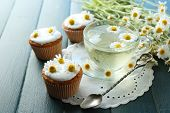 pic of chamomile  - Cup of chamomile tea with chamomile flowers and tasty muffins on color wooden background - JPG