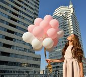 image of high-rise  - Beautiful young girl holding colored balloons over high - JPG