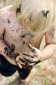 pic of mud  - An overhead view of the Hands of a young child covered in mud as he trys to clean them after playing outside in the dirt - JPG