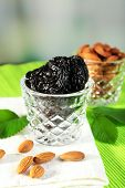 foto of prunes  - Prunes and almonds in glasses with leaves on green napkin - JPG