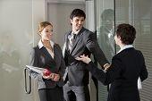 pic of open door  - Three office workers chatting at open door of boardroom  - JPG