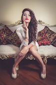 image of mystique  - Pretty model girl wearing white dress sitting on victorian sofa posing for camera looking into camera - JPG