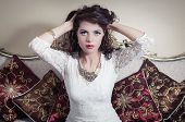 stock photo of mystique  - Pretty model girl wearing white dress sitting on victorian sofa posing for camera while holding her hair up - JPG