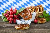 picture of pretzels  - Fresh Bavarian pretzels in a breadbasket and a bunch of red radishes on a wooden table - JPG