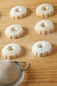 foto of sprinkling  - Regular arrangement of italian canestrelli biscuits on a wooden table with a strainer used to sprinkle powdered sugar - JPG