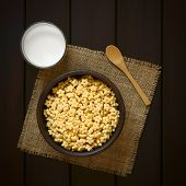 picture of flavor  - Honey flavored breakfast cereal in rustic bowl with a glass of milk and a wooden spoon on the side photographed overhead on dark wood with natural light - JPG