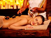 pic of panchakarma  - Young woman having stone massage in salon with burning candle - JPG