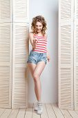 picture of jalousie  - Young beautiful woman wearing jeans shorts and  top posing in front of a jalousie - JPG