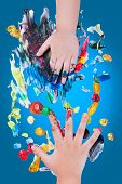 stock photo of finger-painting  - Closeup of little children hands doing finger painting with various colors on blue background art education and creativity concept top view - JPG